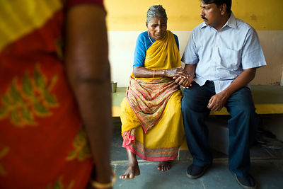India - Cuddalore - an elderly resident talks to Saithyababu (Deputy Director of Help Age India in Cuddalore) about her sore ankle