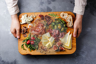 Italian snacks food with Ham, Olive, Cheese, Sun-dried tomatoes, Sausage and Bread on wooden cutting board in male hands on concrete background