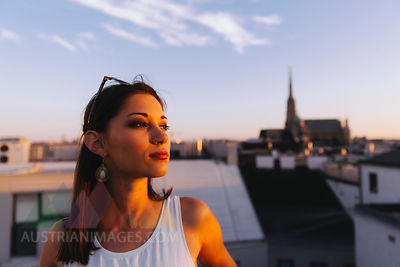 young woman on rooftop at sunset with Stephansdom in the background, Vienna, Austria