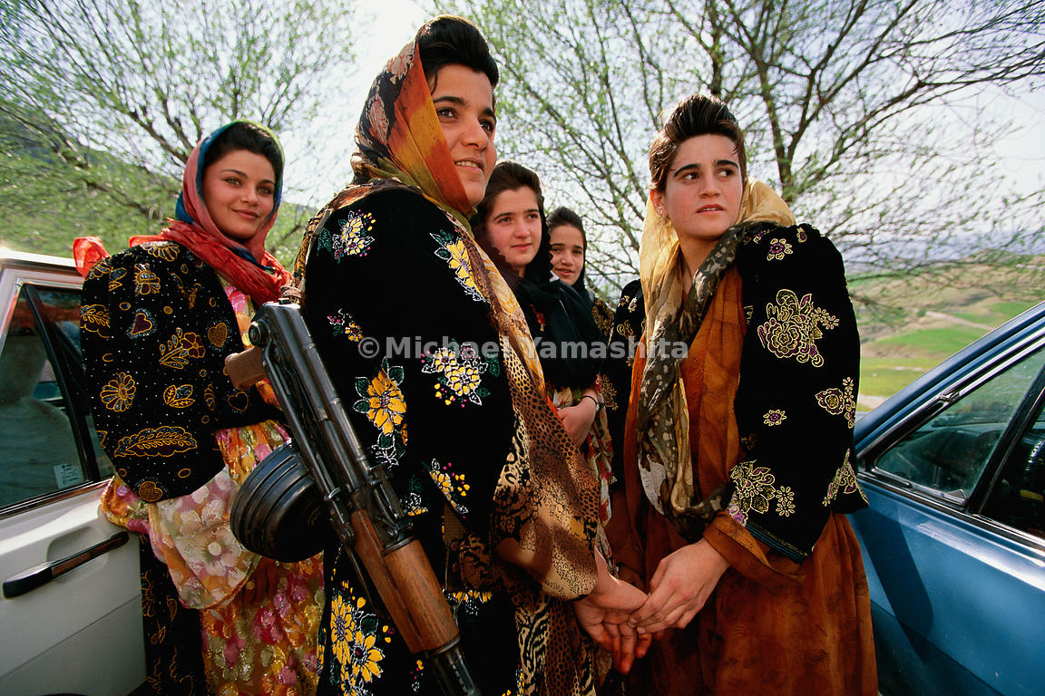 War is never far from the mind of any Kurd, male or female. Dressed in wedding finery, these guests are armed with their AK-47s.  Jundian, Iraqi (Kurdistan)