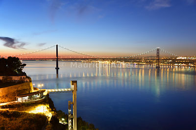 Lisbon and 25 de Abril bridge over the Tagus river, at dusk, seen from Almada. Portugal