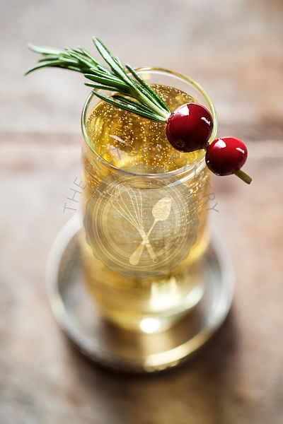 Beautiful champagne drink bubbling in stemless flute with a rosemary and cranberry garnish.