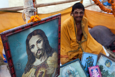A pilgrim sits next to a painting of Jesus at a staging area in Kolkata, India for pilgrims going to the Gangasagar Mela on Sagar Island south of Kolkata.