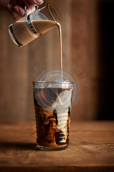 Glass of iced coffee with vintage creamer pouring into the glass on warm wood tones.