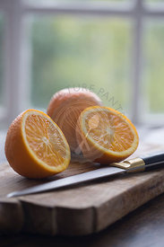 cut oranges on wood baord on table against window framed garden background