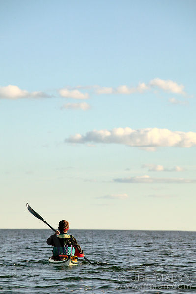 Sea kayaker and beautiful summer clouds
