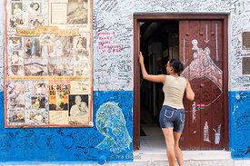 A woman waiting in front of a front door on a street in Old Havana, Cuba.