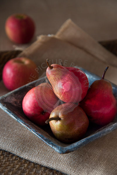 group of red pears in rustic ceramic dish,  on sack cloth and woven tray, red apples in background,