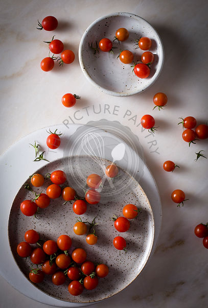 Grape tomatoes in a ceramic plate on top view