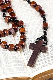 Rosary beads and cross lying on an open page of the bible.