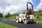 County Council workers laying tarmac on rural road in Cumbria, UK.