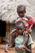 Sad looking Kenyan boy with his young sister sitting on his shoulders. Kenya.