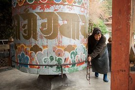 Old woman rotating the large prayer wheel in Punakha, Bhutan.