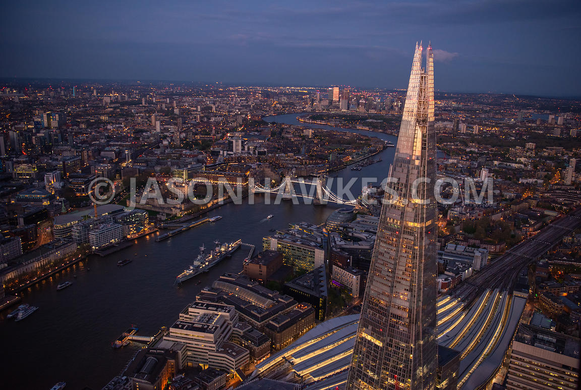 Dusk aerial view of the Shard, River Thames and Tower Bridge looking East to Canary Wharf, London.