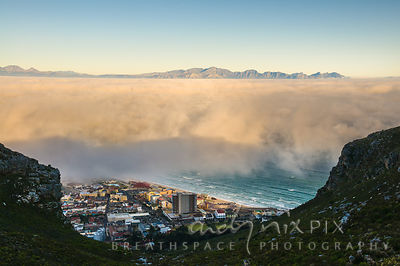 View above fog over False Bay, small patch of beach, sea and village visable  at the foot of the mountain below the cloud, mountains visible in distance above clouds