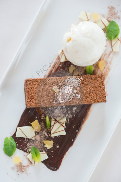 Chocolate brownice served with ice cream and white chocolate.