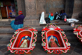 Saints (part of Corpus Christi festival decorations) and beggar outside church, Cusco , Peru