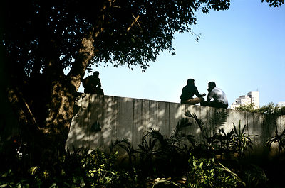 India - Delhi - Men talking on a wall in a park overlooking Palika Bazaar