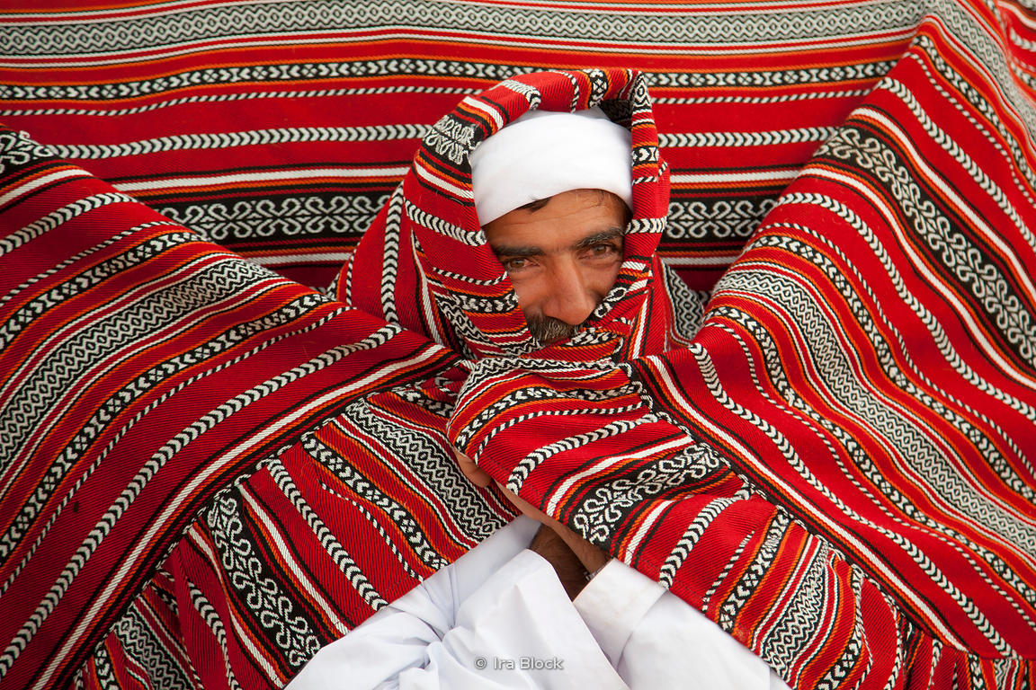 A camel holder wrapped up in a blanket to stay warm at Empty Quarter.