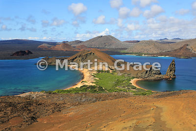 The classic view from the summit viewpoint of Bartolome Island across the western end of Bartolome and Sullivan Bay to the lava flows, cinder cones and tuff cones of Santiago, Galapagos Islands