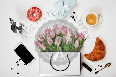 Top view of spring flowers, coffee, mobile phone, croissants, gift and cosmetics. Flat lay image. Holiday, romance of modern life concept