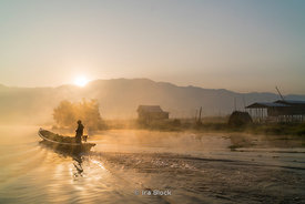A boat approaching a village on Inle Lake, a freshwater lake located in the Nyaungshwe Township of Taunggyi District of Shan State, part of Shan Hills in Myanmar (Burma).