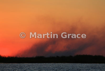 Smoke from bush-fires lit red at sunset, River Chobe, Botswana
