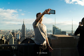 A tourist takes a selfie on the top of the rock in Rockefeller Center, Manhattan, New York City.