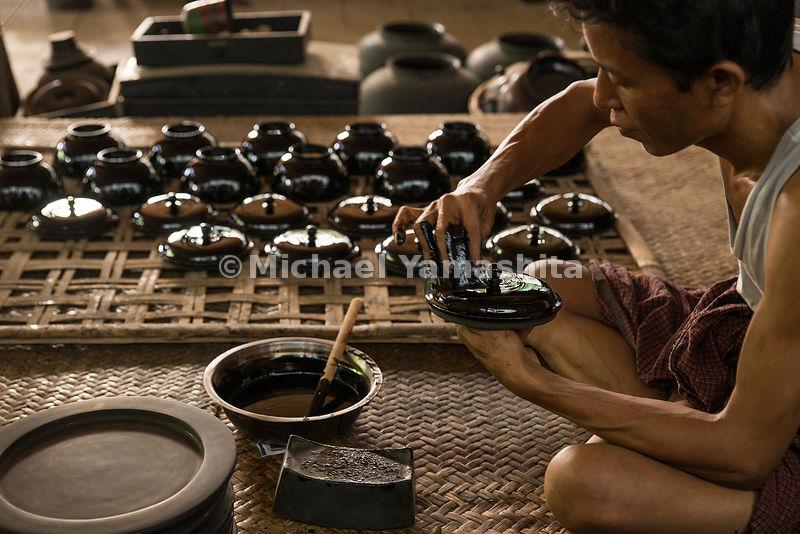 Workers at the U Ba Nyein lacquer shop in Bagan. Here, lacquerware is prepared as it has been for centuries. A varnish made of tree sap is applied to a basin or pot constructed of bamboo, wood and horse hair. Needles are used to etch elaborate designs into the vessel's side.