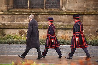 Three men walking in step - Two are Beefeaters
