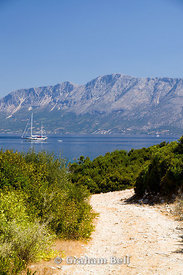 Footpath with view of mountains on mainland Greece from Fanari Point, Meganisi Island, Lefkas, Ionian Islands, Greece