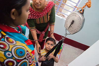 A toddler is weighed at the Swastha Kendra clinic operated by the NGO Calcutta Kids (calcuttakids.org) in the Fakir Bagan area of Howrah, India