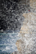 Fisherman on ledge and sea spray