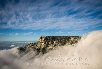 Aerial view of the upper cable station on the cliff edge, sticking out above thick cloud surrounding the mountain, view North towards Bloubergstrand