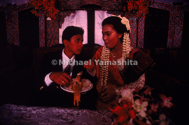 The bride and groom eat from a communal dish. The Batak people, described by Marco Polo as being cannibals are mostly Christian today.