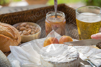 camembert cheese being cut, with apricots, apricot chutney, almonds and beer, set on woven tray