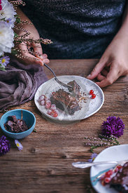 Woman eating chocolate sweet potato brownies served on dessert plates on rustic wooden table
