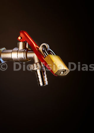 Garden faucet with padlock on dark background