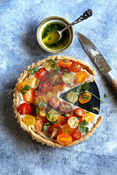 Ricotta heirloom tomato tart on a pan with garlic parsley dressing.Top view
