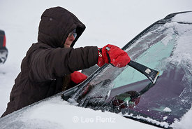 Karen Rentz scrapes ice off the car windshield on Hurricane Ridge while the photographer just stands by, Olympic National Park, Olympic Peninsula, Washington, USA, March, 2009_WA_8192