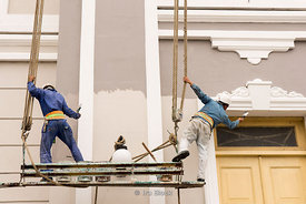 Workers painting the  exterior of a building in Cienfuegos, Cuba.