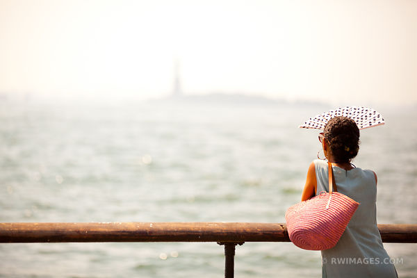 WOMAN LOOKING AT STATUE OF LIBERTY MANHATTAN NEW YORK COLOR