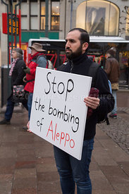 Alleppo Bombing Protestor holding a placard at the Hamburg Rathausmarkt Christmas Market