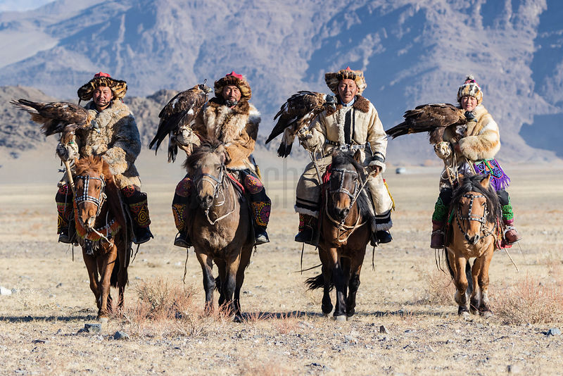 Four Kazakh Golden Eagle Hunters Approach the Festival Site from across the Gravel Plain