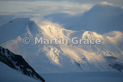 Spectacular sunlight on mountains in Marguerite Bay, West Graham Land, Antarctica with glacier, cloud and blue sky