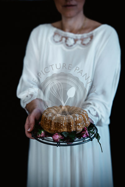 A woman holding a pear cake on a cake stand.