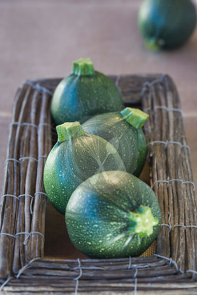 round cougettes ,or zucchini, in a woven box on mat covered table,