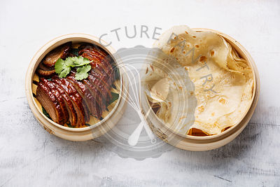 Sliced Peking Duck in bamboo steamer served with fresh roasted wheaten chinese pancakes on white background