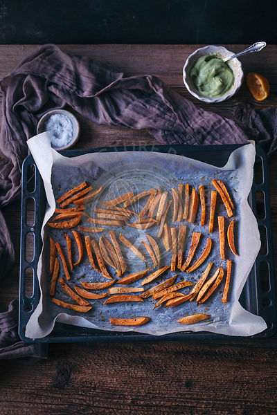 Oven baked sweet potatoes fries on a baking tray