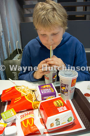Young boy eating at a fast food resturant, UK.